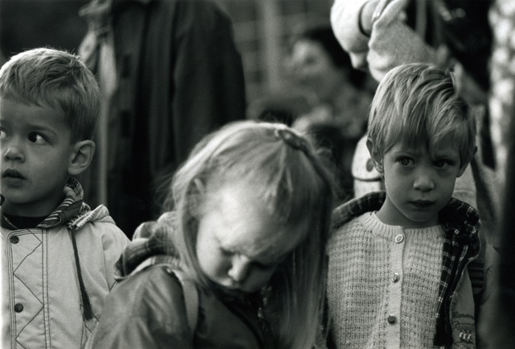 Three children in a row. All looking anxious.