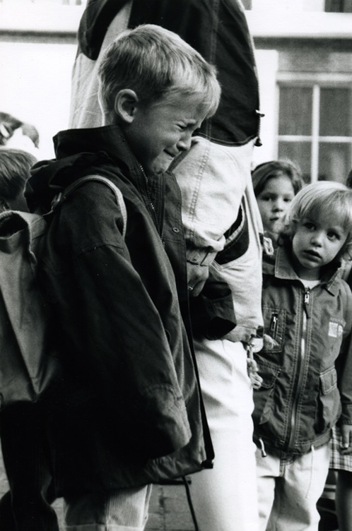 A little boy biting his lip and trying very hard not to cry - but failing. A little girl is looking at him.