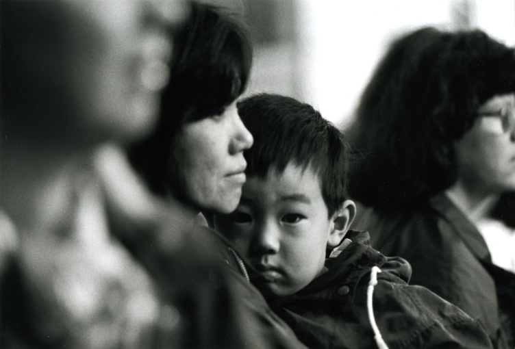 A mum looking into the distance, her son - cuddled up close to her - looking straight in the camera. He looks a little anxious.